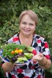 Gelukkige gepensioneerdevrouw met groenten bij dacha Stock Afbeelding