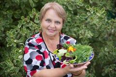 Gelukkige gepensioneerdevrouw met groenten bij dacha Stock Foto's