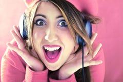 Gelukkige geschokte vrouw in het roze luisteren aan goed geluid Royalty-vrije Stock Fotografie