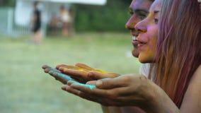 Gelukkige gezichten van beste vrienden die poederverf blazen in de lucht bij Holi-festival stock video