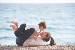 Gelukkige gezonde uit glimlachende moeder bestaan en vrolijke familie die weinig kind die en op overzees strand in de vroege zome Stock Afbeeldingen