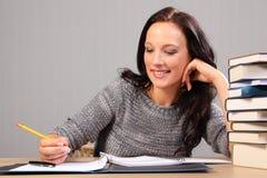 Gelukkige glimlach die thuiswerk voor mooie vrouw doet Stock Foto