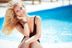 Gelukkige glimlachende aantrekkelijke blonde vrouw over blauw water die po zwemmen Royalty-vrije Stock Foto