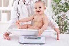 Gelukkige glimlachende baby in pedricianbureau, die gewicht meten Stock Foto's