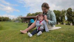 Gelukkige glimlachende babyjongen die pret met moeder hebben bij park stock video