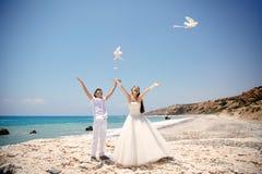 Gelukkige glimlachende bruid en bruidegomhanden die witte duiven op een zonnige dag vrijgeven Middellandse Zee cyprus Stock Afbeeldingen