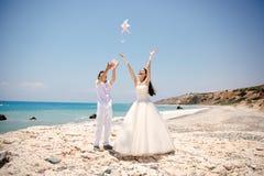Gelukkige glimlachende bruid en bruidegomhanden die witte duiven op een zonnige dag vrijgeven Middellandse Zee cyprus Stock Afbeelding