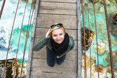 Gelukkige glimlachende en ontspannende vrouw op een dagtocht die zich op een oude houten hangende brug bevindt royalty-vrije stock foto