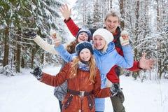 Gelukkige glimlachende familie in de winter sneeuwbos royalty-vrije stock afbeeldingen