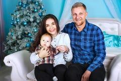 Gelukkige glimlachende familie dichtbij de Kerstboom home-like atmosfeer, het Nieuwjaar en het Kerstmisontwerp stock foto