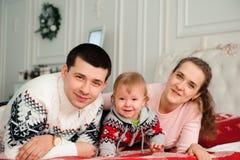 Gelukkige glimlachende familie met één jaarzoon dichtbij de Kerstmisachtergrond stock foto