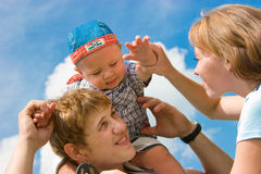 Gelukkige glimlachende familie op blauwe hemelachtergrond Royalty-vrije Stock Foto's