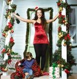 Gelukkige glimlachende familie op Kerstmis bij huis met giften, jonge moeder en weinig zoon in de rode hoed van Santas, levenssti royalty-vrije stock afbeeldingen
