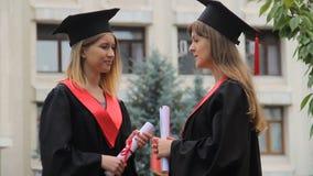 Gelukkige glimlachende gediplomeerden die dichtbij academie babbelen en diploma's, gesprek houden stock video