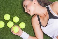 Gelukkige Glimlachende Gelooide Vrouwelijke Sportvrouw die op Kunstmatige Gras liggen Stock Foto