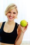 Gelukkige glimlachende geschikte vrouw die groene appel houden Royalty-vrije Stock Afbeeldingen