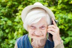 Gelukkige glimlachende grootmoeder die op mobiele telefoon spreken royalty-vrije stock fotografie