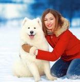Gelukkige glimlachende heldere vrouw met Samoyed-hond in openlucht Royalty-vrije Stock Foto