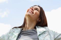 Gelukkige glimlachende jonge aantrekkelijke vrouw over blauwe hemel Royalty-vrije Stock Foto's