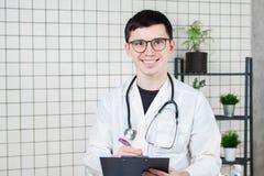 Gelukkige glimlachende jonge arts die op klembord in het modern ziekenhuis schrijven stock afbeeldingen