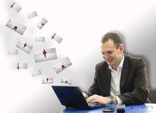 Gelukkige glimlachende zakenman die laptop in bureau voor brieven met behulp van Royalty-vrije Stock Afbeeldingen