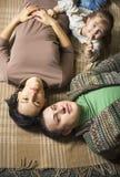 Gelukkige glimlachende jonge familie die op de vloer liggen Stock Foto's