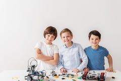 Gelukkige glimlachende jonge technici dichtbij bureau Royalty-vrije Stock Afbeeldingen