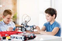 Gelukkige glimlachende jonge technici die speelgoed maken Royalty-vrije Stock Foto's