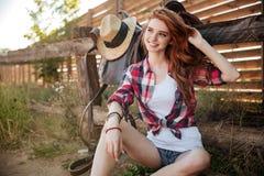 Gelukkige glimlachende jonge veedrijfster die bij de boerderijomheining rusten Stock Fotografie