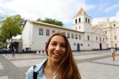 Gelukkige glimlachende jonge vrouw in de stadscentrum van Sao Paulo met Patio do Colegio oriëntatiepunt op de achtergrond, Sao Pa stock afbeeldingen