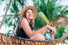 Gelukkige glimlachende jonge vrouw in de zitting van de strohoed in hangmat met palmenachtergrond royalty-vrije stock afbeelding
