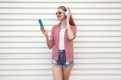 Gelukkige glimlachende jonge vrouw die in hoofdtelefoons met smartphone aan muziek luisteren die geruit overhemd, borrels op wit  royalty-vrije stock afbeelding