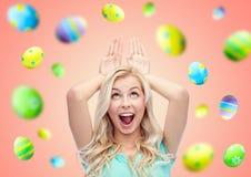 Gelukkige glimlachende jonge vrouw die Pasen-konijntjesoren maakt stock foto