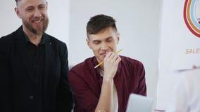 Gelukkige glimlachende jonge zakenman die het werk bespreken met collega's tijdens moderne bureauvergadering, gezonde werkplaats stock videobeelden