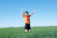 Gelukkige glimlachende jongen die hoog, groen gras en blauwe hemel op de achtergrond, het succes, het fortuin, de voltooiing en h royalty-vrije stock fotografie