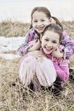 Gelukkige glimlachende koesterende zusters op gebied Stock Foto's