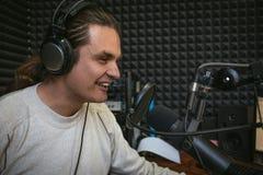 Gelukkige glimlachende mannelijke radiopresentator of gastheer met hoofdtelefoons op hoofd die in microfoon in radiostation, port stock foto