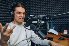 Gelukkige glimlachende mannelijke radiopresentator of gastheer met hoofdtelefoons op hoofd die in microfoon in radiostation, port royalty-vrije stock foto's
