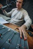Gelukkige glimlachende mannelijke radiopresentator of gastheer met hoofdtelefoons op hoofd die in microfoon in radiostation, port stock afbeeldingen