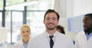 Gelukkige Glimlachende Mannelijke Wetenschapper Walk In Laboratory over de Onderzoekers Team In Modern Lab van het Mengelingsras stock footage