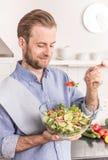 Gelukkige glimlachende mens die verse groentesalade in de keuken eten royalty-vrije stock fotografie