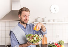 Gelukkige glimlachende mens die verse groentesalade in de keuken maken royalty-vrije stock afbeelding