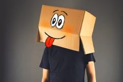Gelukkige glimlachende mens met kartondoos op zijn hoofd Royalty-vrije Stock Afbeelding
