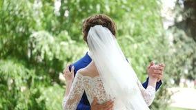 Gelukkige glimlachende modieuze bruid en bruidegom die in het de zomer groene park lopen met boeket van bloemen, en pret hebben d stock footage