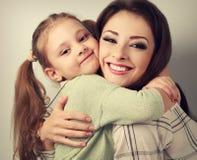 Gelukkige glimlachende moeder die speels emotioneel jong geitjemeisje in nagel knuffelen stock fotografie