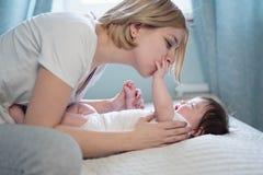Gelukkige glimlachende moeder en baby die op bed thuis liggen royalty-vrije stock afbeelding