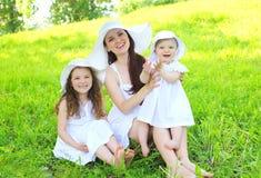 Gelukkige glimlachende moeder en twee kinderen die witte kleding en strohoeden dragen Stock Afbeeldingen