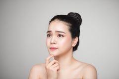 Gelukkige glimlachende mooie Aziatische vrouw wat betreft haar gezicht stock fotografie
