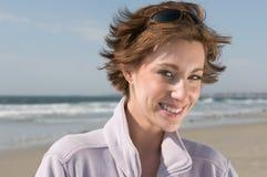 Gelukkige, glimlachende mooie jonge vrouw bij het strand Royalty-vrije Stock Foto's