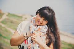 Gelukkige glimlachende mooie te zware jonge vrouw in witte T-shirt en sjaal met anker in openlucht dichtbij aan overzees Zekere v Stock Afbeeldingen